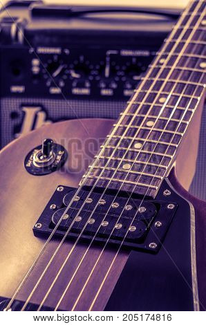Part electric guitar and classic amplifier on a dark background.
