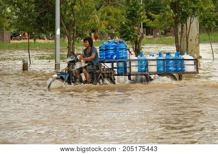 Delivery Motorcycle Rides Through Flooded Streets
