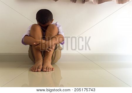 LIttle Asian boy sad and depressed sitting in the room Abuse concept.