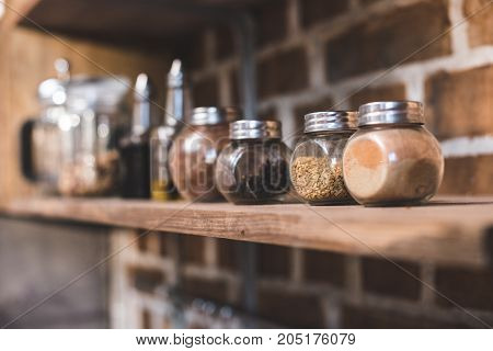 selective focus of arranged jars with various spices on kitchen shelf