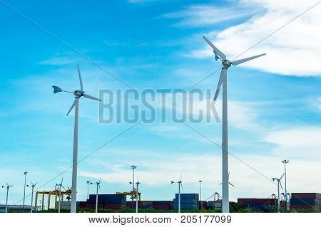 Wind turbine or windmill generating electricity on blue sky background