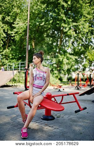 Sport Girl Wear On White Shorts Ans Shirt Doing Exercises On Simulators Outdoor At Park.