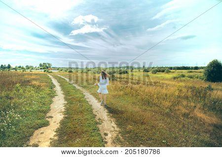 Girl in summer field. Blue sky, tall grass
