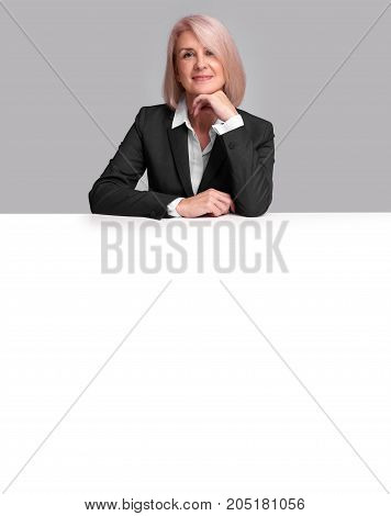 Middle Aged Businesswoman Sitting At The Desk