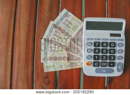 Calculator and money thai banknote on wooden table at home office. The concept of financial planning savings