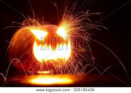 Halloween Pumpkin with sparks On A Black Background
