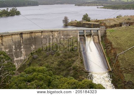 Concrete arch dam with water spilling out the ski-jump spillway backed by a very full reservoir at the Myponga Reservoir in Myponga South Australia. Middle of winter 2017.