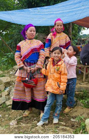 North Vietnamese Women In Colorful Native Clothing With Children In Western Garb