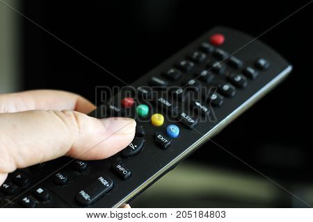 the TV remote in a female hand