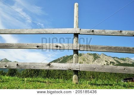 Wooden fence in the Alps under blue sky