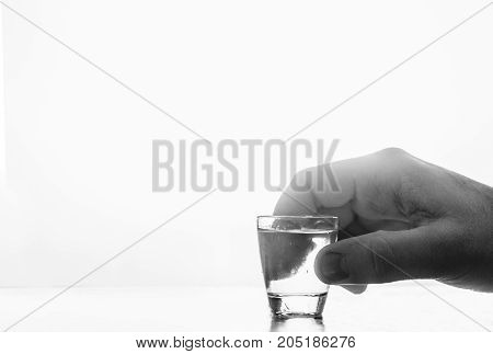 Man's hand holding a glass with vodka