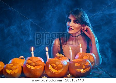 Beautiful witch with Halloween pumpkins over blue smoky background with backlight looking to the side at blank copy space