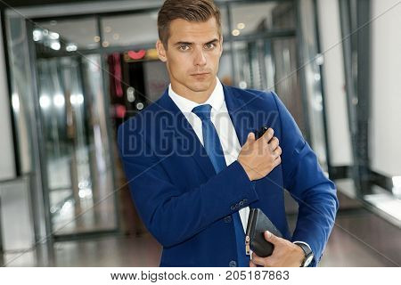 A handsome man in a blue suit and tie inside a modern building