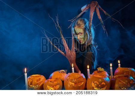 Halloween costume woman, tree girl, female with hands branches with burning pumpkins in front of her on smoky background