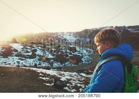 little boy enjoy hiking in snow winter mountains