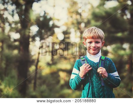 little boy with backpack enjoy travel in green forest, kids hiking and sport orienteering