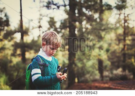 little boy travels with compass in green forest, sport orienteering