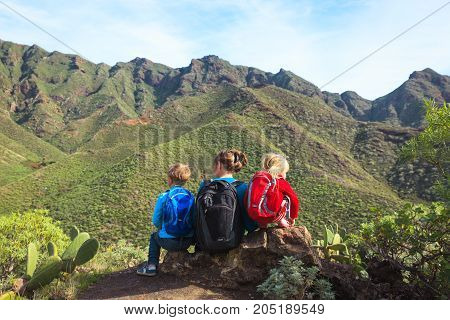 mother with two kids hiking in mountains, family travel