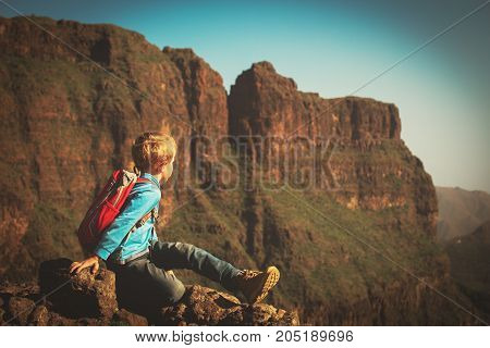 little boy travel hiking in mountains looking at scenic view