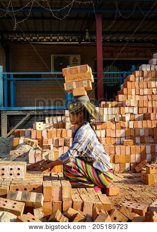 Woman Carrying Brick At Construction Site
