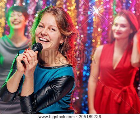 Group of young pretty smiling women having fun at karaoke