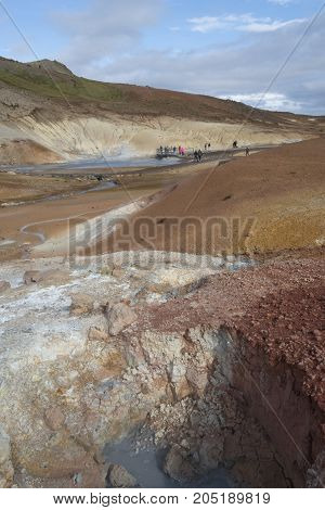 Multicolored geothermal area in Iceland. Blue sky in background.