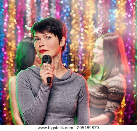 Young excited happy women celebrating in karaoke bar