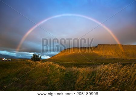 Landscape with golden grass mountain and rainbow. Iceland. Car travel.