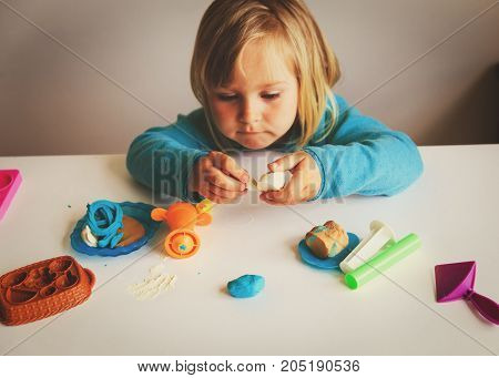 Child playing with clay molding shapes, kids learning
