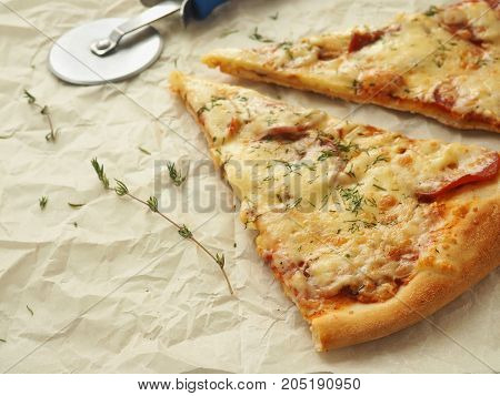Culinary background with two pieces of  pepperoni pizza upon baking parchment. Homemade pizza with thyme. Copy space for your text. Selective focus.