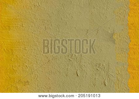 Closeup of bright yellow painted stone wall background, seamless texture