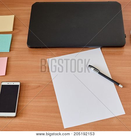 Office workplace with laptop, smartphone, sheet of paper and pen on wooden table