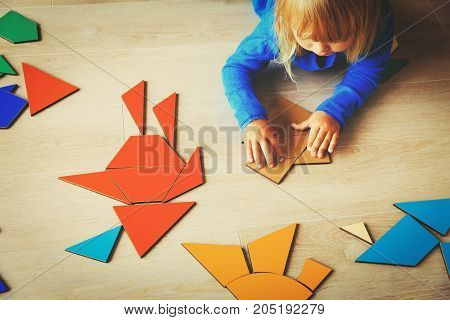 little girl playing with puzzle in school or daycare, early child development