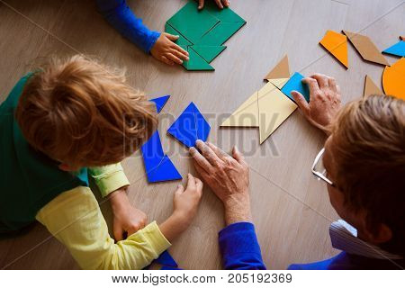 teacher and kids playing with geometric shapes in school or daycare