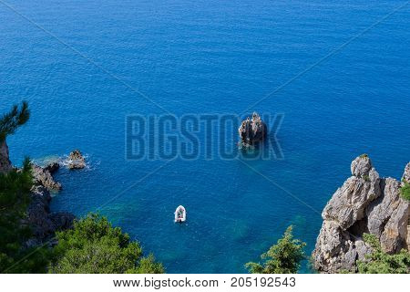 small inflatable boat in the sea at the rocky coast of Corfu, Greece