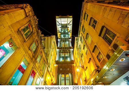 Lisbon, Portugal - August 24, 2017: scenic iron structure of Santa Justa Elevador also called Carmo, an elevator connecting Baixa district to Barrio Alto illuminated at night. Architecture background.