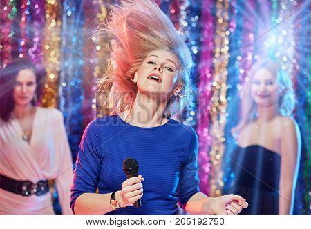 Group of cheerful pretty girlfriends celebrating party at karaoke