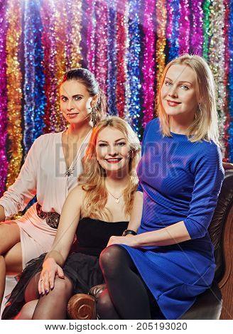 Portrait of three beautiful women celebrating in night club