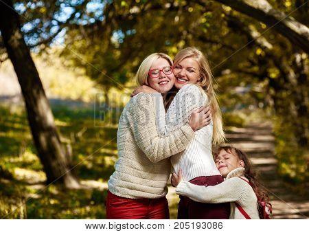 Three cute happy sisters hugging in autumn park