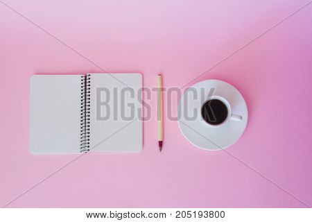 Top view of blank notebook pen and cup of coffee over pink background.