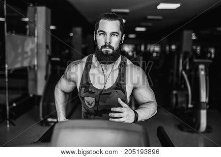 Fit Muscle Bearded Man With Headphones Running on Treadmill in Gym.