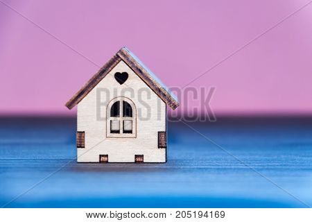 Miniature wooden toy house on a wooden table with a colored background