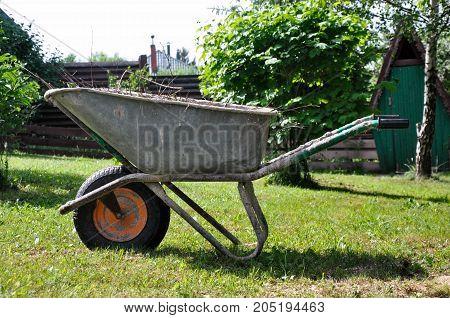 Garden wheelbarrow in the village on green grass
