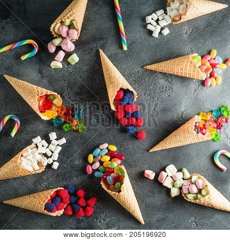 Pattern with colorful bright assorted candy in waffle cones on dark background. Flat lay, top view