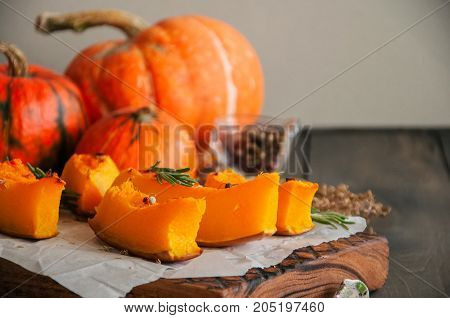 Roasted Pumpkin Slices With Rosemary And Dry Thyme On A Baking Paper On A Wooden Background.
