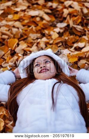 Autumn girl playing in city park. Portrait of an autumn woman lying over leaves and smiling outside in fall forest. Beautiful energetic Asian young woman