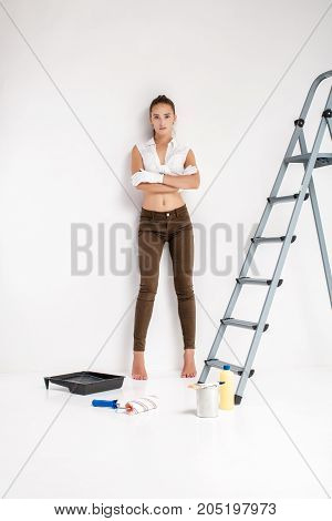 beautiful attractive woman ready to paint a wall in her house