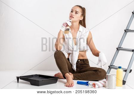 beautiful attractive woman painting a wall in her house