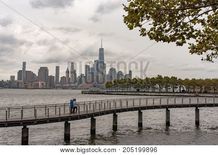 Hoboken NJ USA -- September 19 2017 A couple strolls along a promenade over the Hudson River with the New York skyline in the background . Editorial Use Only.