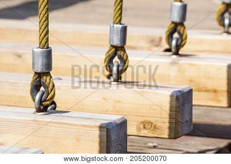 Old wooden swing so rusty on hook .